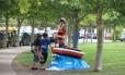 """Dois """"pibes"""" observam a escultura do marinheiro Langostino e seu barco Corina em Puerto Madero"""