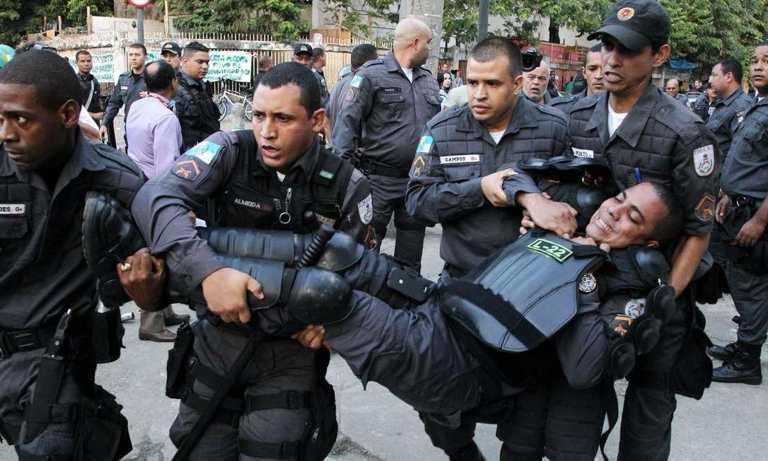 Policial ferido é socorrido durante o confronto com os invasores do prédio e terreno da operadora Oi Foto: Fernando Quevedo / Agência O Globo