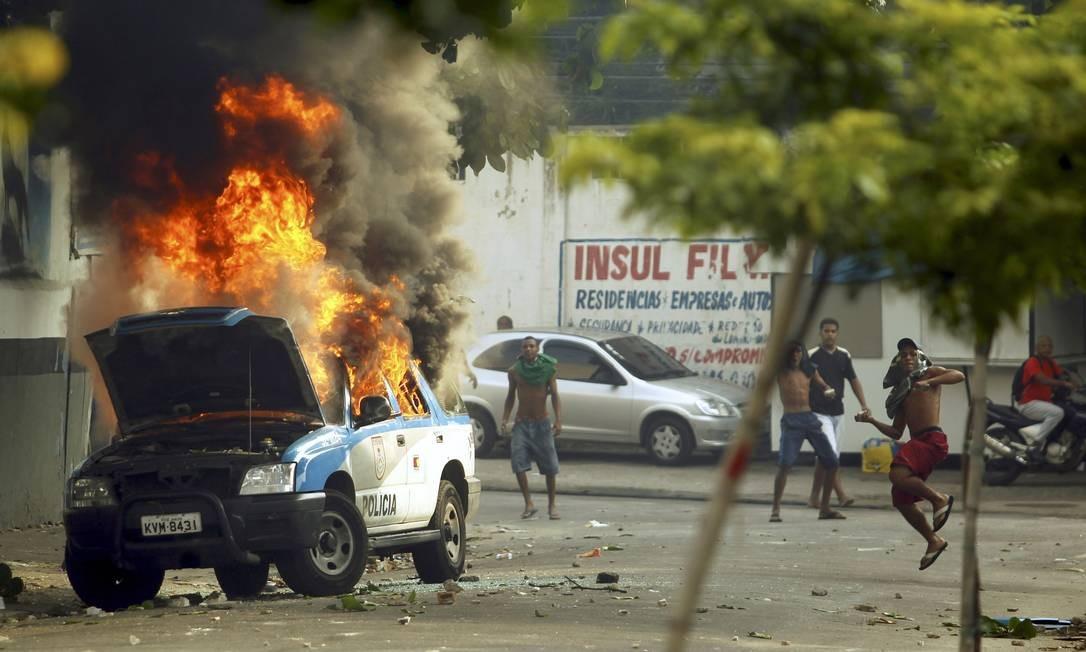 Um carro da PM é incendiado durante conflitos na desocupação da favela da Telerj. Inavasores atiram pedras em direção à polícia Foto: Gabriel de Paiva / Agência O Globo