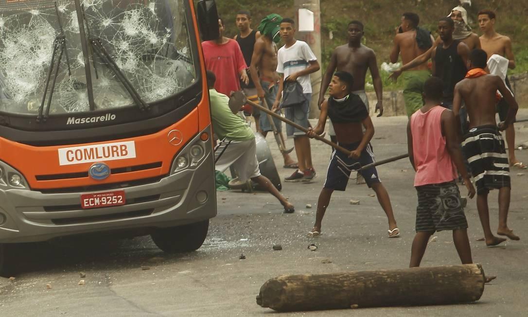 Armados com paus e pedras, moradores atiraram objetos contra policiais militares dando início do confronto, por volta das 6h Foto: Gabriel de Paiva / Agência O Globo