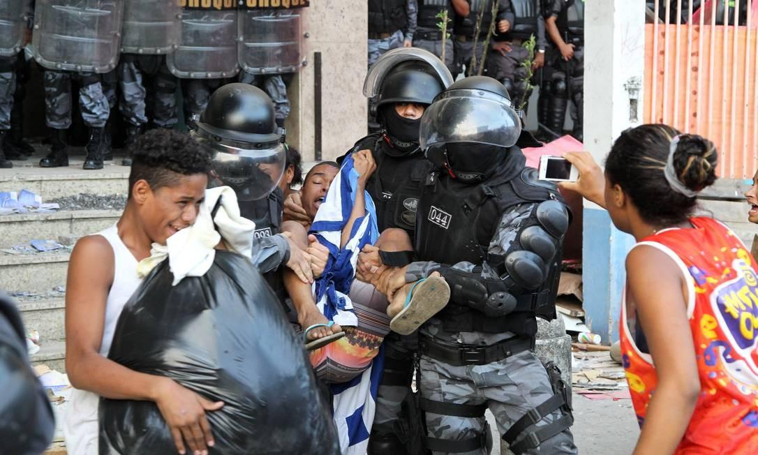 Policiais retiram pessoas que ocupam o prédio da operadora Oi, durante a reitegração de posse Foto: Fernando Quevedo / Agência O Globo