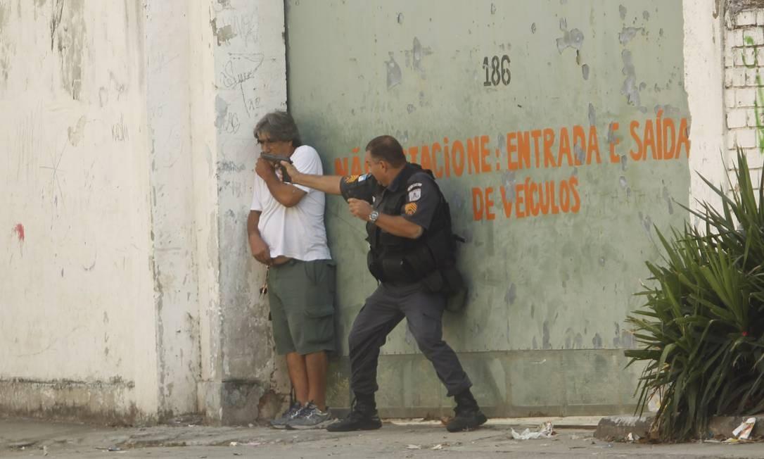 Policial atira em direção aos manifestantes, na frente de um homem que passava pelo local Foto: Gabriel de Paiva / Agência O Globo
