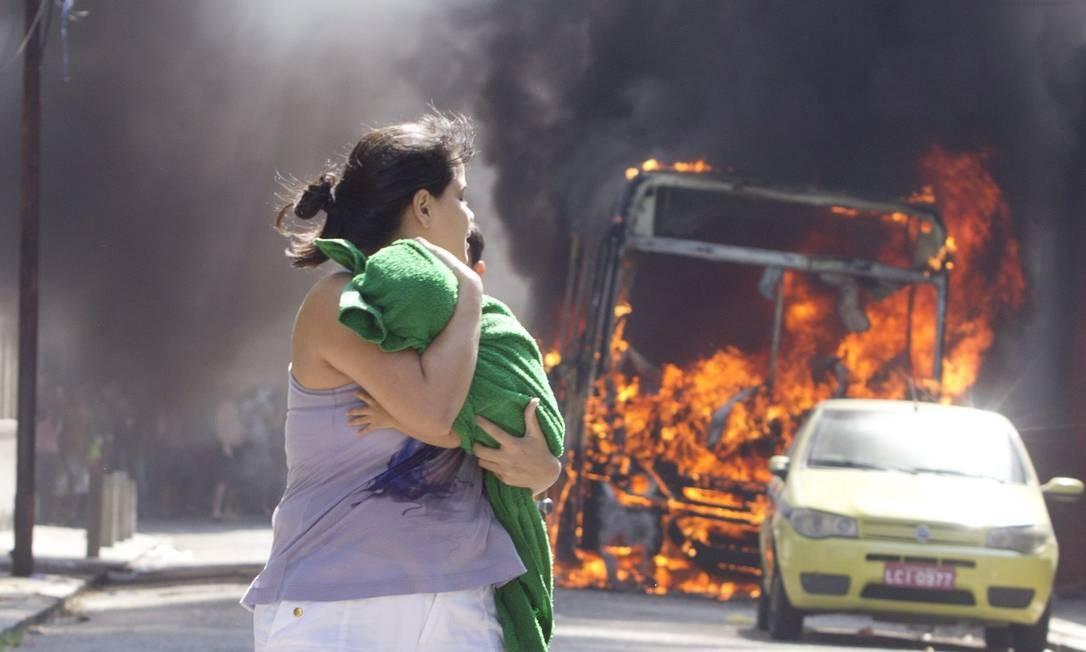 RI Rio de Janeiro (RJ) 11/04/2014 Desocupação do prédio da Oi no Engenho Novo. Na foto, mulher corre com bebê no colo assutada com ônibus pegando fogo a poucos metros do prédio. Márcia Foletto / Agência Globo Foto: Márcia Foletto / Agência O Globo