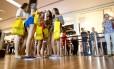 Adolescentes esperam na entrada da loja Forever 21, recém-aberta no shopping Village Mall, na Barra da Tijuca: batata frita na lanchonete, fotos nas redes sociais e até dever de casa para distrair nas 3 horas de espera