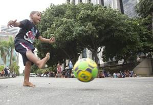 Menino joga bola próximo à sede da prefeitura Foto: Márcia Foletto / Agência O Globo