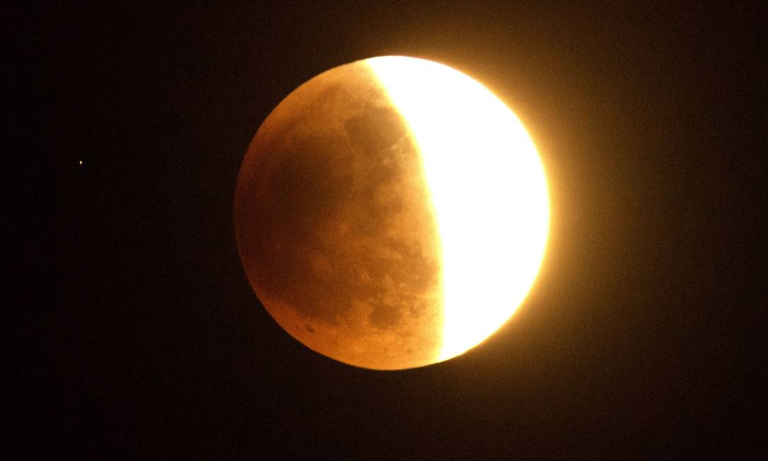 Essa Lua, no meio do eclipse, foi vista avermelhada no Sul da Califórnia JOE KLAMAR / AFP