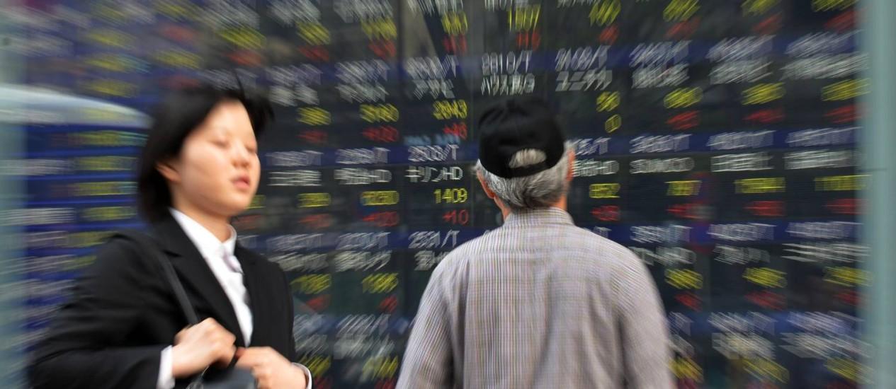 Homem olha para painel com valores de câmbios monetários em Tóquio: receita do país ficou comprometida com diminuição da força de trabalho Foto: YOSHIKAZU TSUNO / AFP