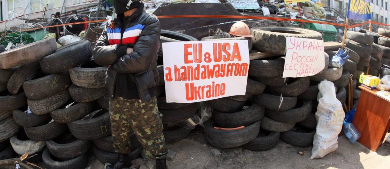 Separatista monta guarda em uma barricada em Mariupol. No cartaz, pede que EUA e UE 'mantenham as mãos longe da Ucrânia' Foto: Alexander KHUDOTEPLY / AFP