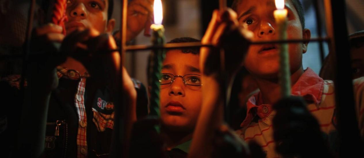 Protesto. Meninos seguram velas atrás de grades falsas durante manifestação em solidariedade aos prisioneiros palestinos, na Faixa de Gaza Foto: IBRAHEEM ABU MUSTAFA / REUTERS