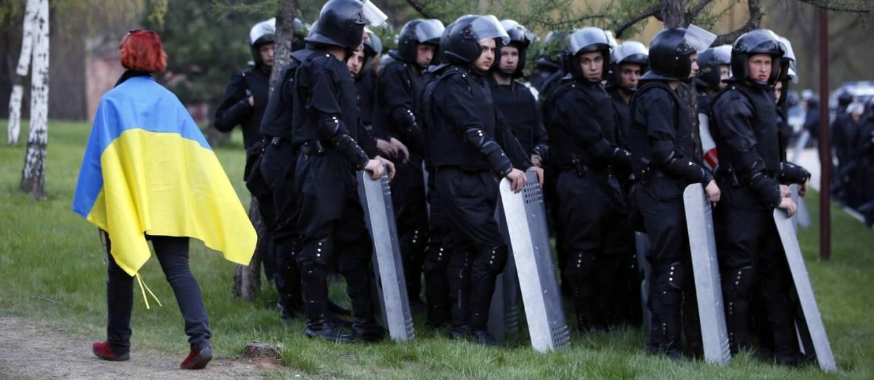 Donetsk. Policiais ucranianos posicionados enquanto manifestante pró-Kiev passa enrolado na bandeira ucraniana. Estados Unidos enviarão equipamento às forças de segurança do país Foto: MARKO DJURICA / REUTERS