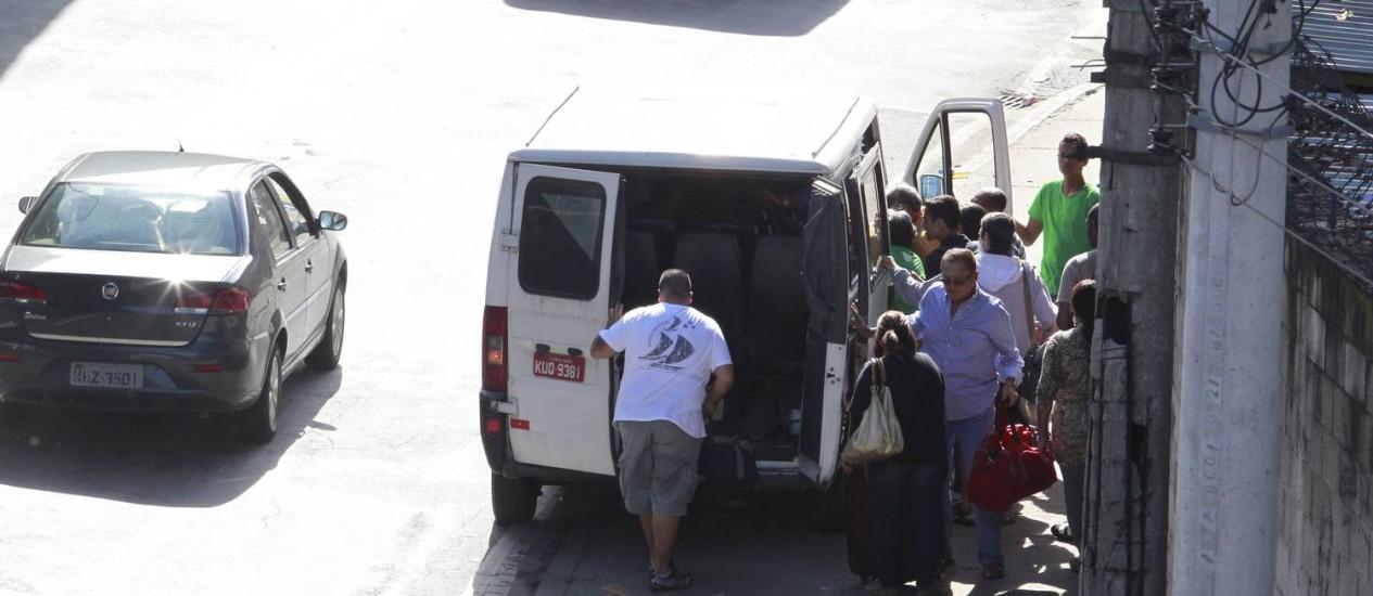 Agenciador leva grupo de passageiros pelo meio da rua até uma van descaracterizada na Avenida Francisco Bicalho Foto: Domingos Peixoto / Agência O Globo