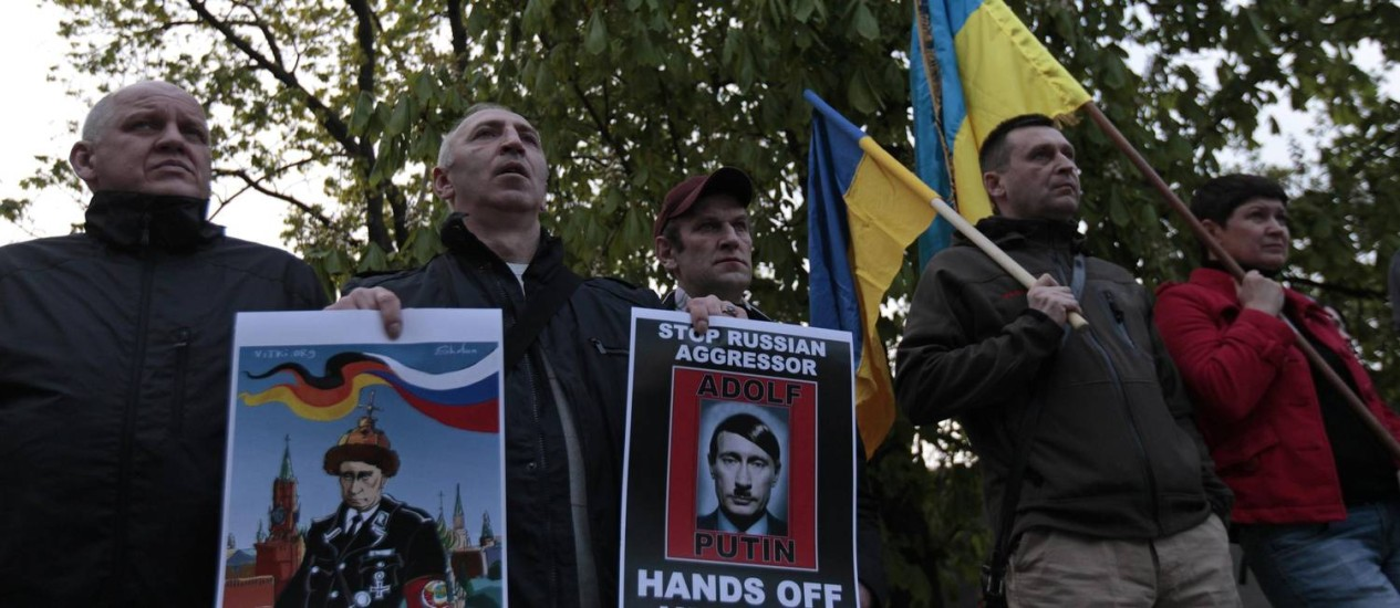 Praga. Manifestantes pró-Kiev carregam cartaz que compara presidente russo Vladimir Putin a Adolf Hitler, em manifestação na frente da embaixada russa na capital tcheca Foto: DAVID W CERNY / REUTERS