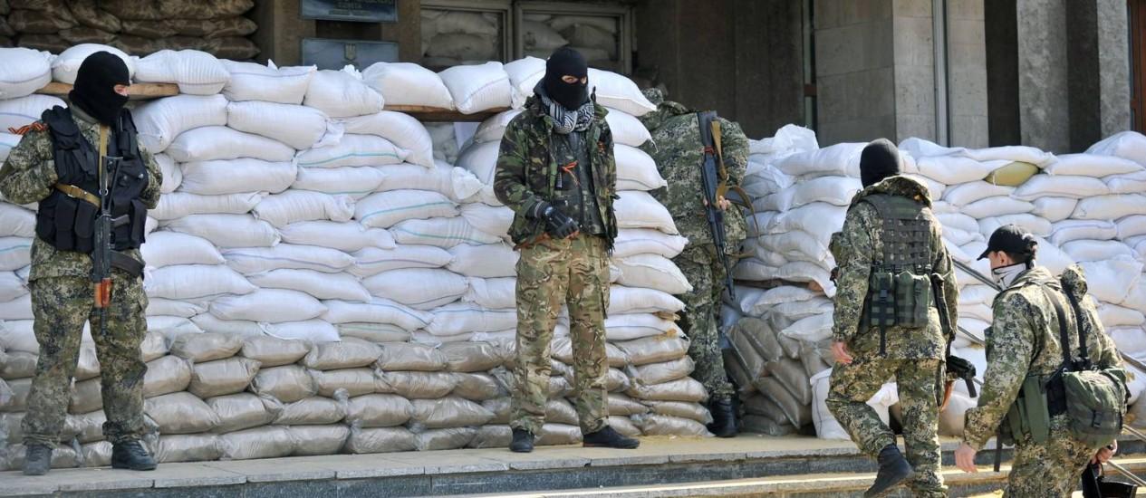 Homens armados fazem guarda em um edifício público em Slaviansk, no Leste da Ucrânia Foto: GENYA SAVILOV / AFP