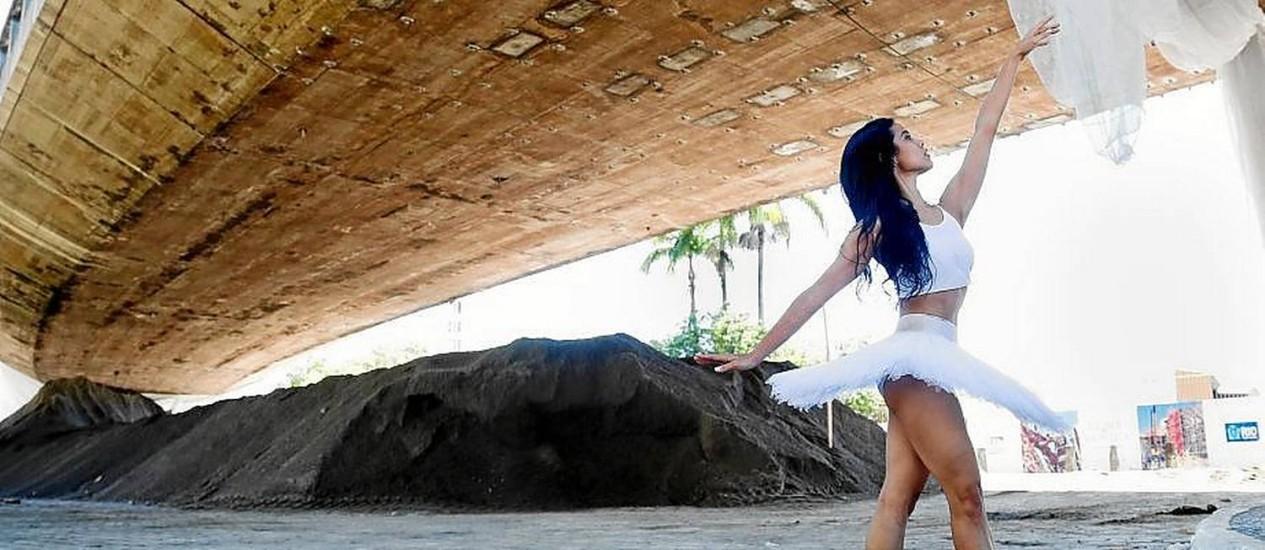Balé. Com os cabelos soltos e sapatilha, bailarina Liana Vasconcellos dança sob a Perimetral Foto: Simone Marinho / Simone Marinho