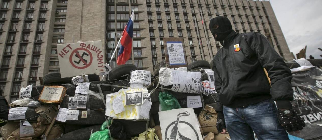 Rebelde pró-Rússia mascarado guarda barricada na entrada de um prédio público em Donetsk, no Leste da Ucrânia: operações contra separatistas foram temporariamente suspensas pelo governo de Kiev Foto: BAZ RATNER / REUTERS/BAZ RATNER