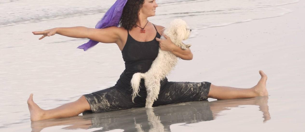 Suzi Teitelman e seu cão praticam doga numa praia dos Estados Unidos Foto: /Divulgação