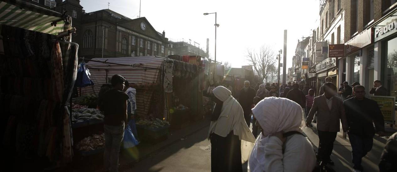 Pedestres passam em frente a barracas em vizinhança próxima ao centro financeiro de Londres: as cinco famílias mais ricas do país têm mais dinheiro do que os 12,6 milhões mais pobres Foto: Matthew Lloyd/Bloomberg/Arquivo