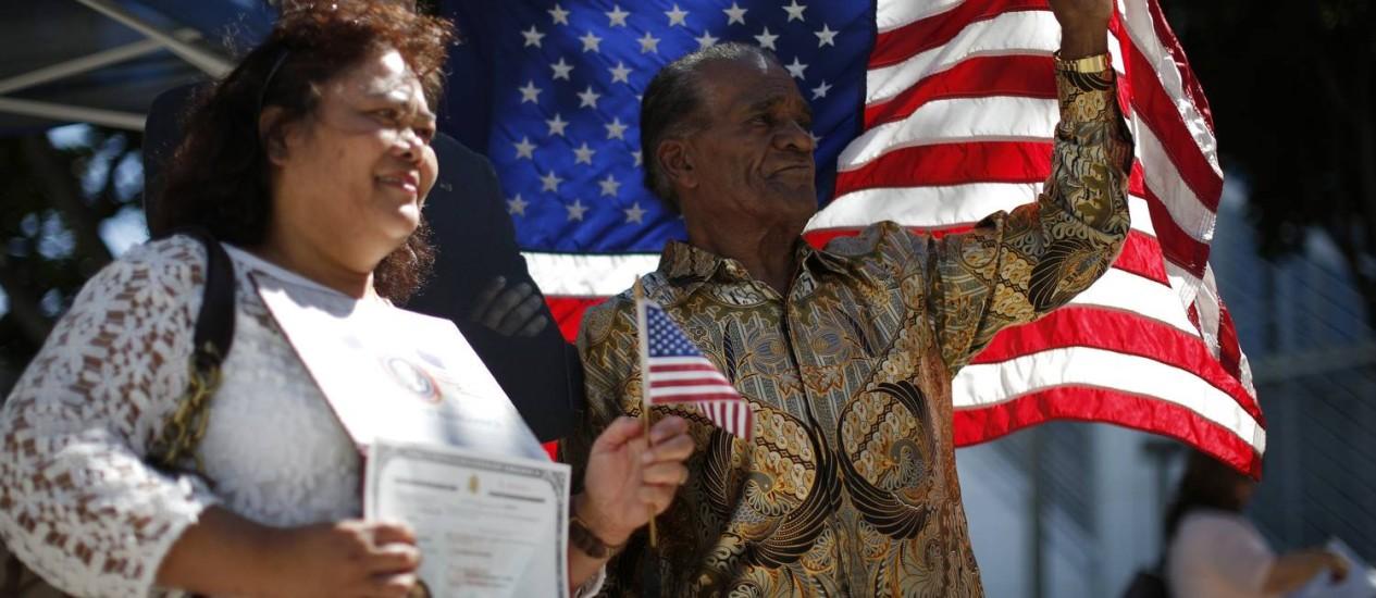 Teste final. Homem e mulher posam próximos à bandeira dos EUA em cerimônia de naturalização em Los Angeles: estrangeiros que obtêm green card ainda precisam passar por exame com perguntas sobre História do país Foto: LUCY NICHOLSON / REUTERS