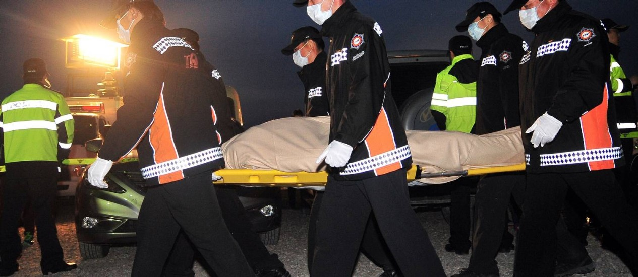 Membros da equipe de resgate carregam corpos de vitimas de naufrágio na Coreia do Sul Foto: JUNG YEON-JE / AFP