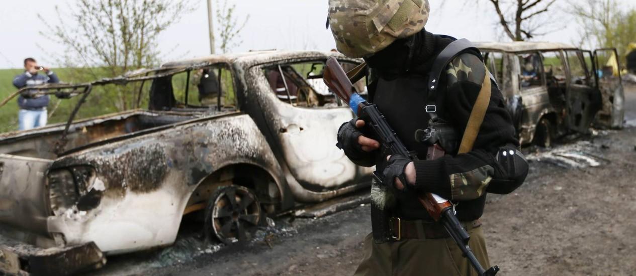 Militante pró-Rússia armado passa por carros queimados em um posto de controle próximo da cidade de Slaviansk, palco do tireoteio que deixou quatro mortos neste domingo Foto: GLEB GARANICH / REUTERS/GLEB GARANICH
