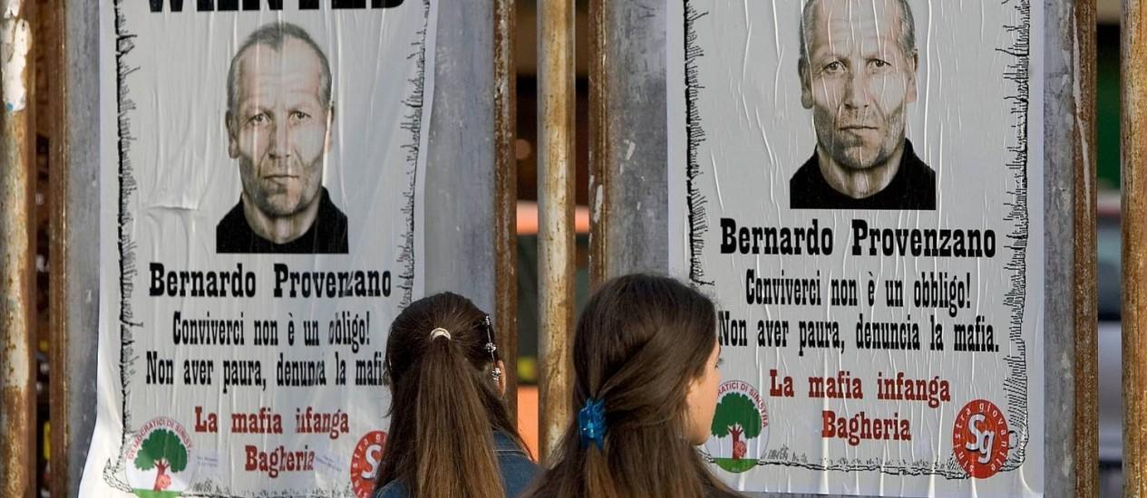 Mulheres observam cartazes sobre busca do chefão da máfia siciliana Bernardo Provenzano: líder máximo da Cosa Nostra foi preso, e organização tem enfrentado problemas com a prolongada crise econômica na Europa Foto: Fabrizio Villa / AFP/28-4-2005