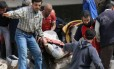 Civis carregam uma mulher ferida após ataque no distrito de Sakhur, em Aleppo