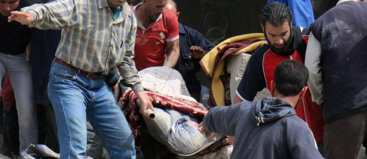 Civis carregam uma mulher ferida após ataque no distrito de Sakhur, em Aleppo Foto: ZEIN AL-RIFAI / AFP