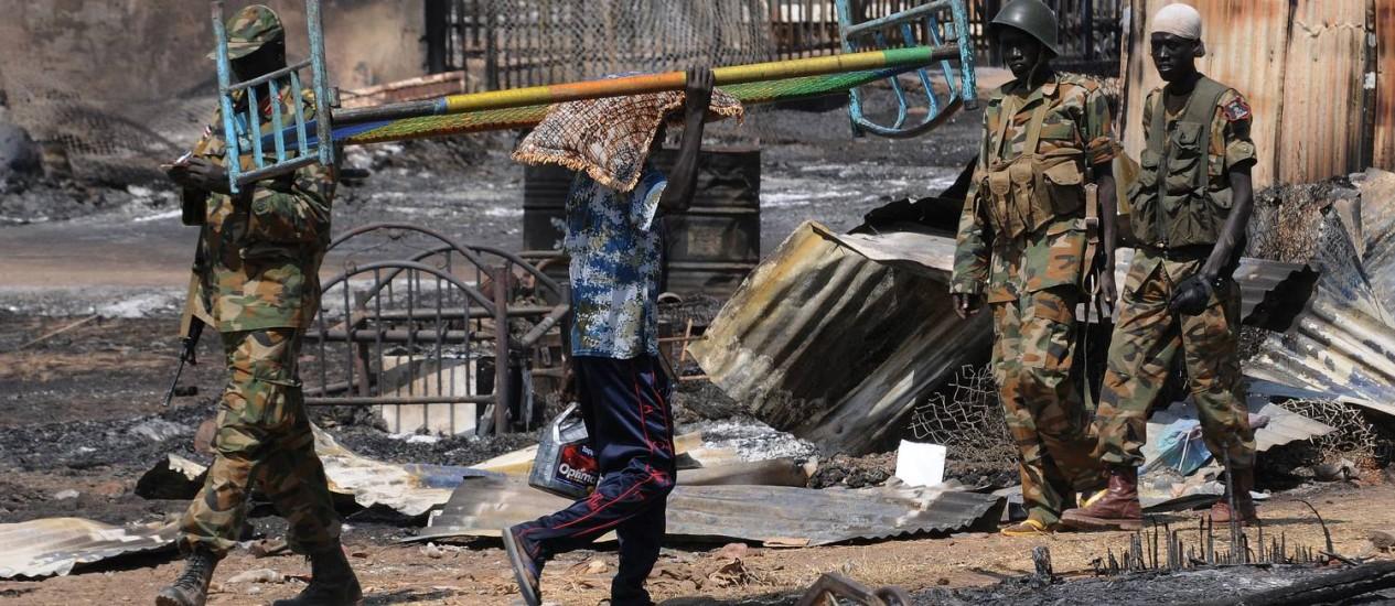 Homens carregam destroços em Bentiu, no Sudão do Sul Foto: SIMON MAINA / AFP