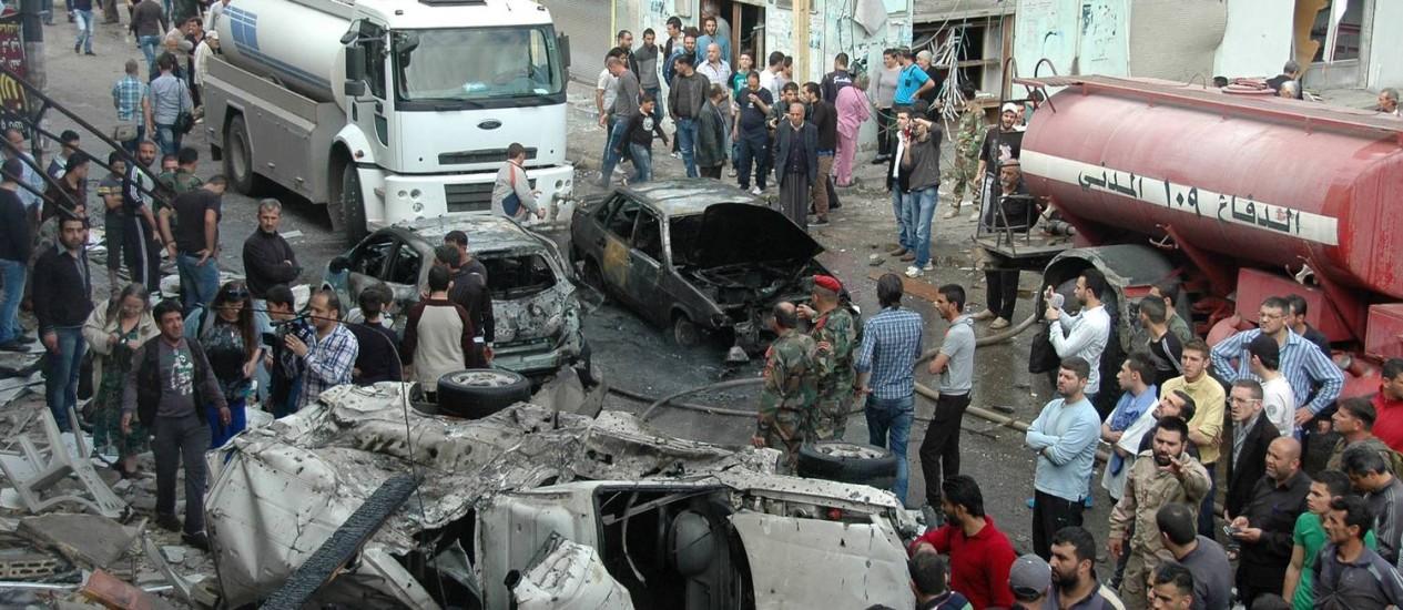 Serviços de emergência trabalham em local de explosão de um carro bomba no bairro de Ekremah. na cidade de Homs Foto: - / AFP/14-4-2014