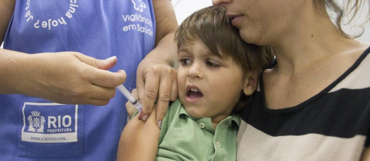 Na foto, Rafael Polimeni, de 4 anos, no colo da mãe, é vacinado no posto de saúde da Rua Siqueira Campos, em Copacabana Foto: Márcia Foletto / Agência O Globo
