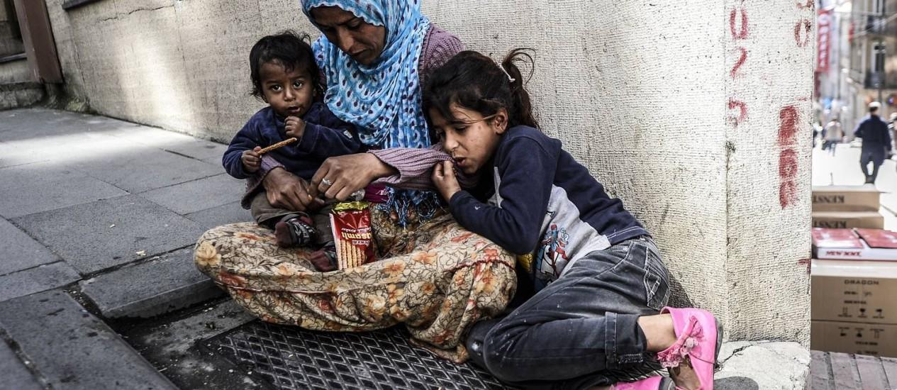 Mulher síria com os filhos em uma calçada no centro de Istambul, capital da Turquia Foto: BULENT KILIC / AFP