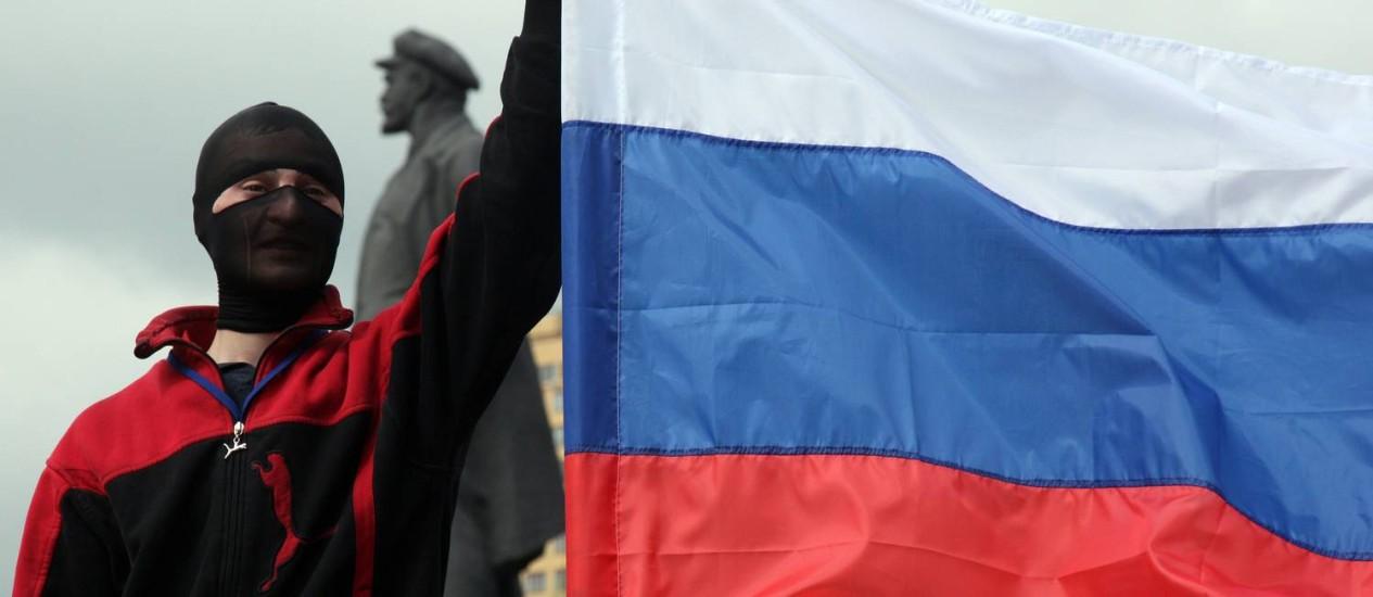 Um separatista segura uma bandeira russa, diante de uma estátua de Lênin, na cidade ucraniana de Donetsk Foto: ANATOLII STEPANOV / AFP