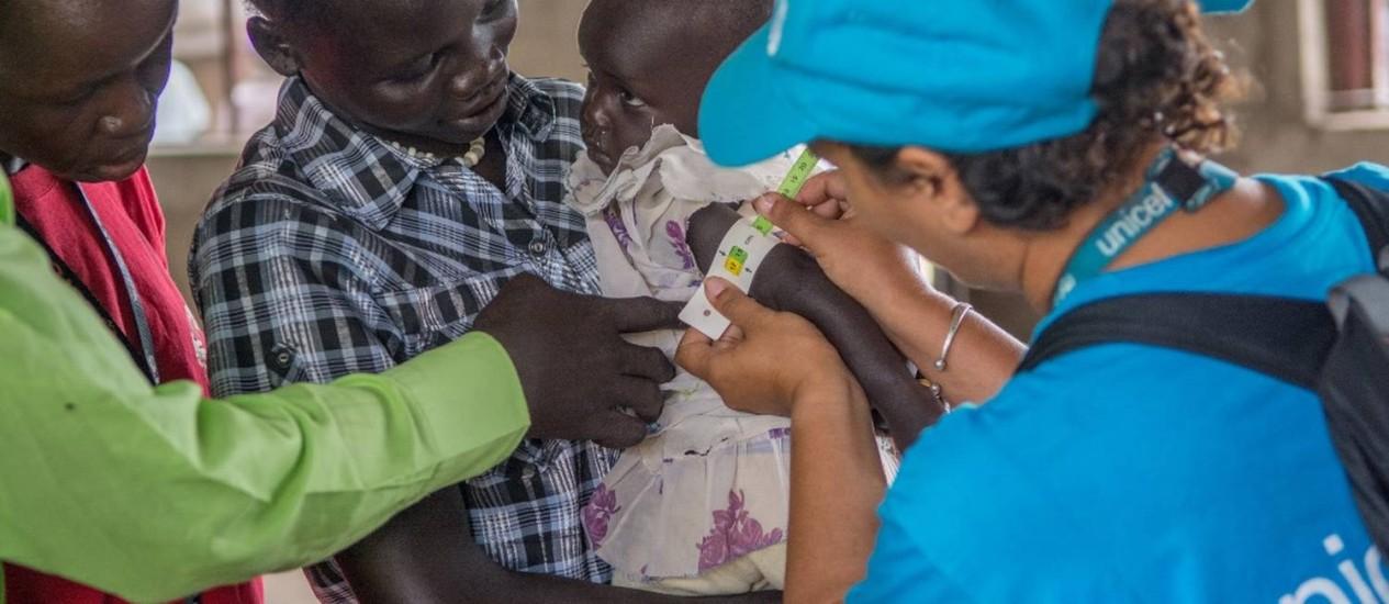Especialista em nutrição do Unicef tira medidas de uma criança para verificar a possibilidade de desnutrição Foto: Dan Alder