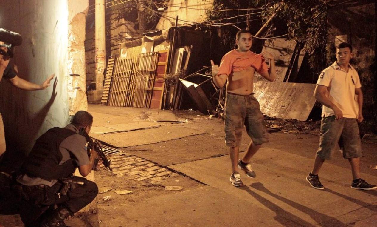 Jovens descem ladeira e passam ao lado de PMs Foto: Marcelo Piu / Agência O Globo