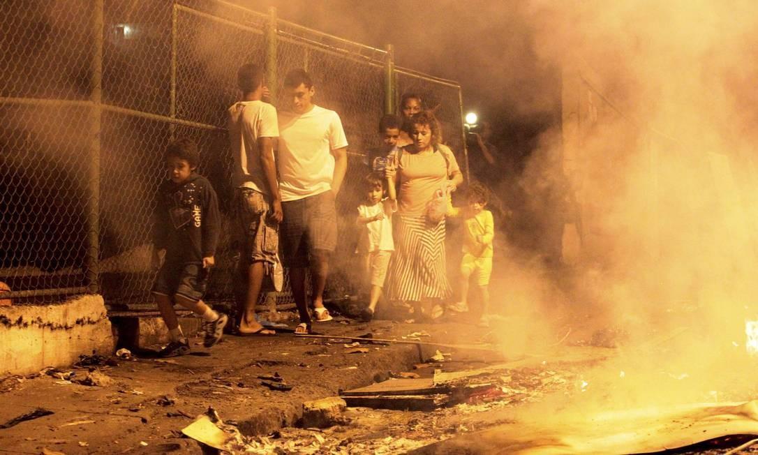 Moradores passam pela rua cheia de fumaça Foto: Marcelo Piu / Agência O Globo