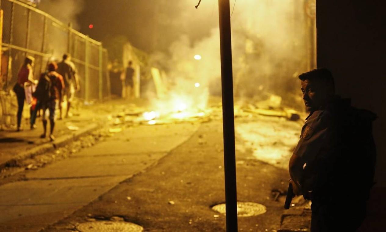 Armado, policial observa a movimentação na Rua Saint Roman, que dá acesso ao morro Foto: Guito Moreto / Agência O Globo