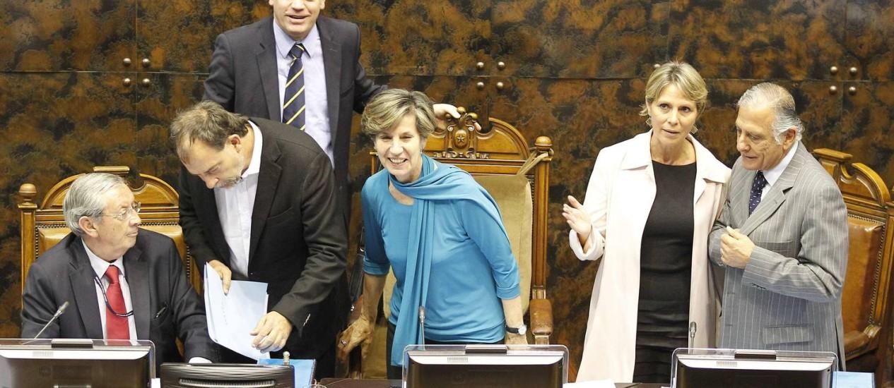 A presidente do Senado Isabel Allende (centro), filha do falecido ex-presidente Salvador Allende, sorri ao lado de outros parlamentares após a aprovação da lei Foto: Eliseo Fernandez / REUTERS