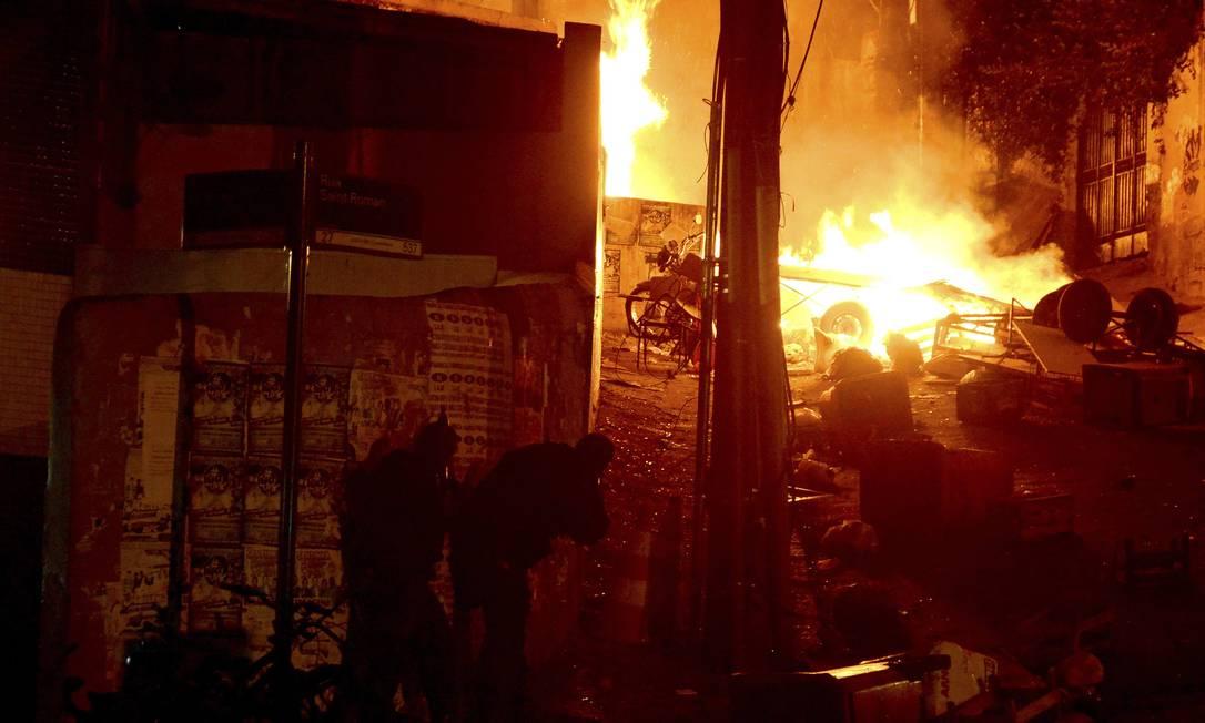 Policiais se protegem do tiroteio na subida da Saint Roman, com lixo pegando fogo ao fundo STRINGER/BRAZIL / REUTERS