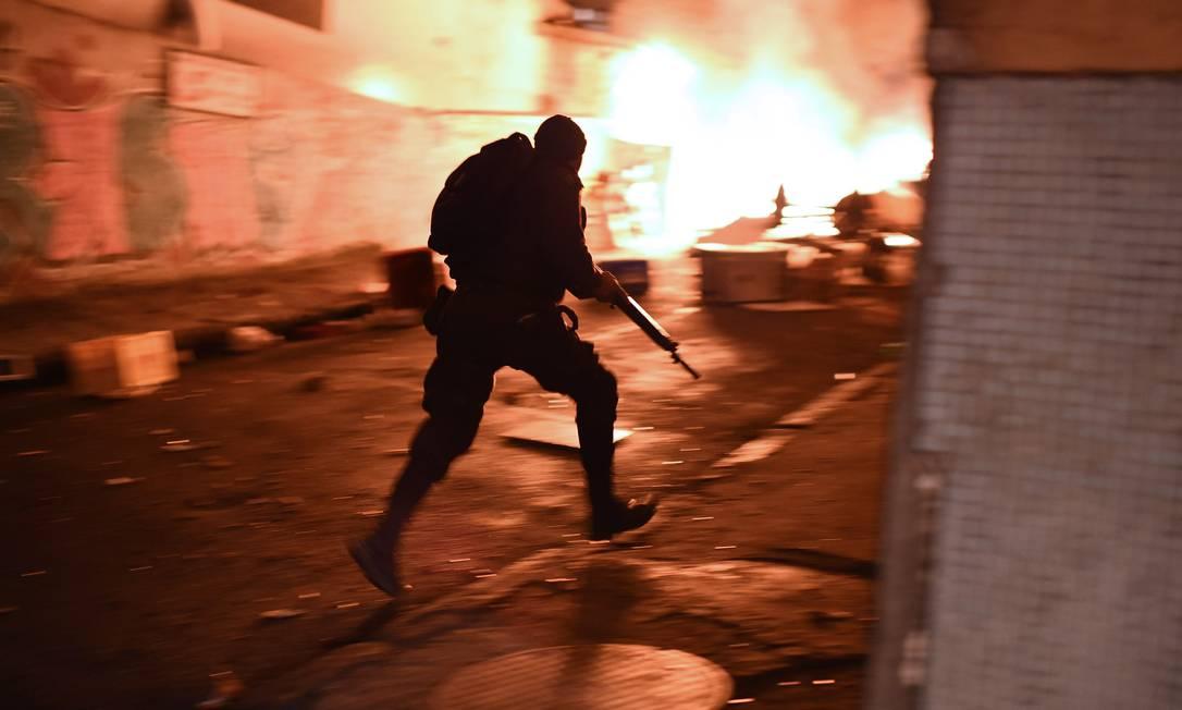 Policial corre para se posicionar na subida do morro CHRISTOPHE SIMON / AFP