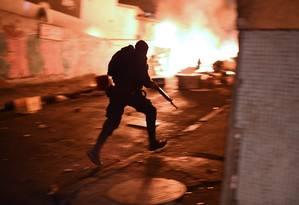 Policial corre para se posicionar na subida do morro Foto: CHRISTOPHE SIMON / AFP