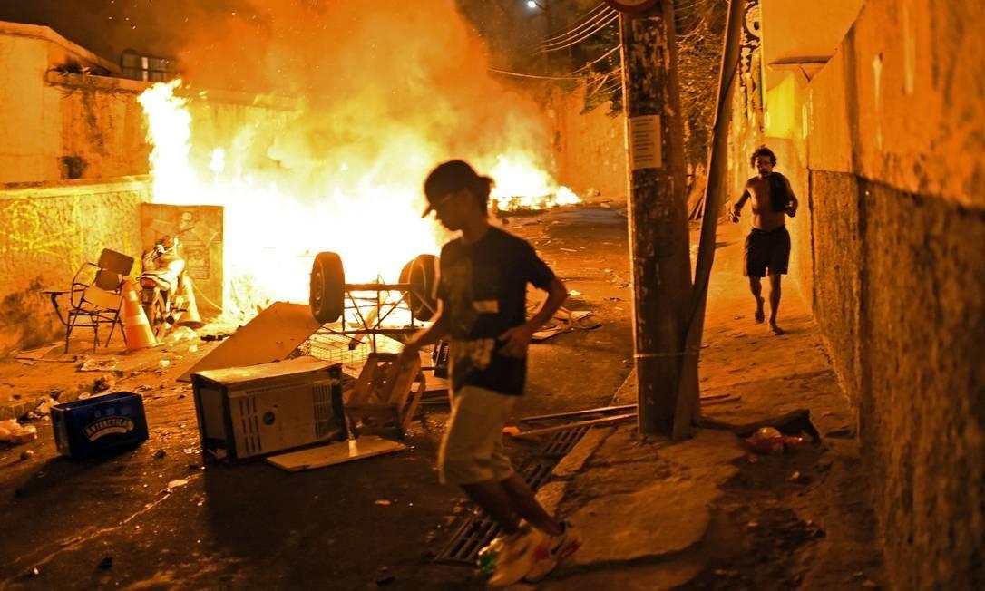 Moradores correm dos tiros e do incêndio na ladeira Foto: CHRISTOPHE SIMON / AFP