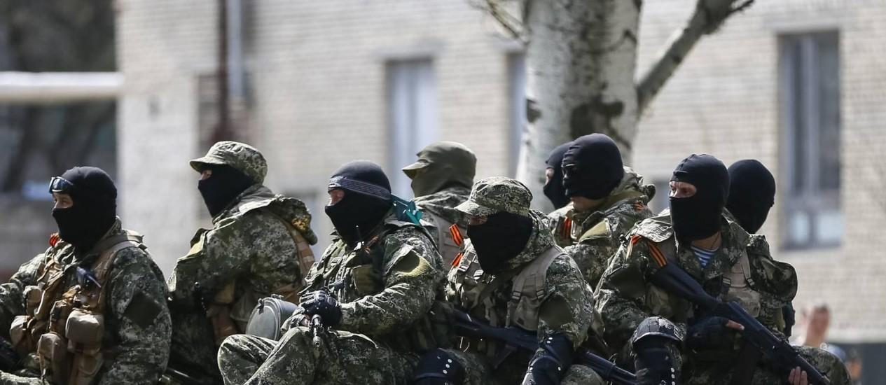 Homens armados, usando fitas pretas e laranja do St. George - um símbolo amplamente associado com os protestos pró-russos na Ucrânia -, dirigem um veículo blindado em Slaviansk Foto: GLEB GARANICH / REUTERS