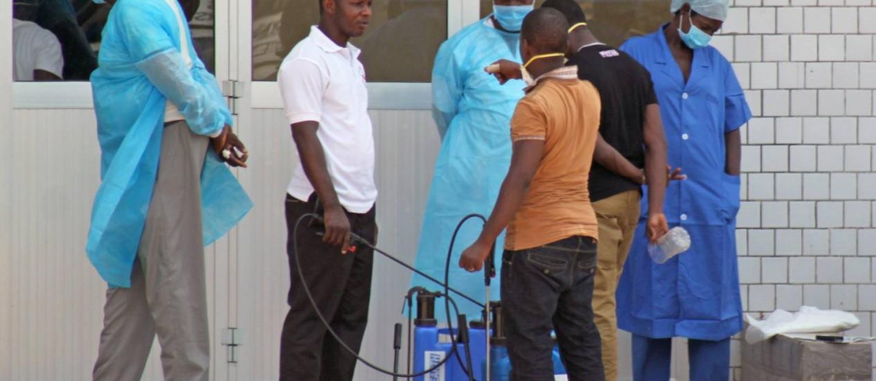 Equipe médica trabalha em frente a hospital de emergência montando na Guiné Foto: AP Photo/Youssouf Bah