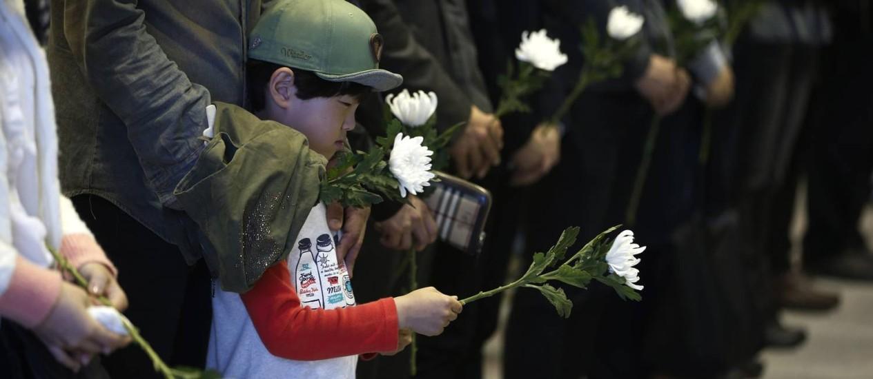 Um menino segurando uma flor presta homenagem às vítimas do naufrágio na Coreia do Sul Foto: KIM HONG-JI / REUTERS
