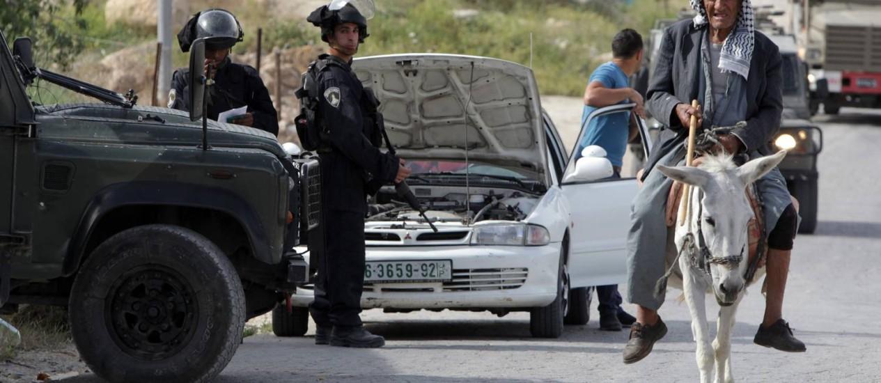 Um palestino passa por soldados israelenses em Der Samet, na Cisjordânia Foto: HAZEM BADER / AFP