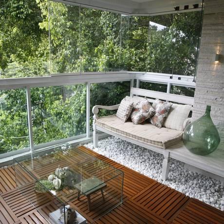 À vontade. A varanda de Debye Rangel tem deque de madeira e decoração com pedras Foto: Eduardo Naddar / Eduardo Naddar