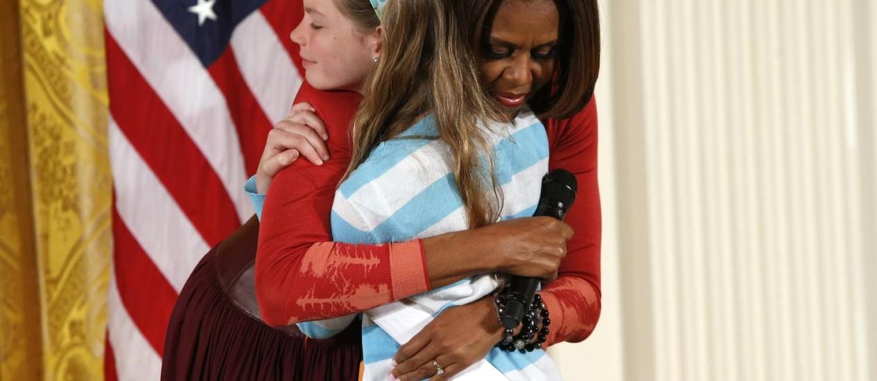 Michelle Obama abraça a menina Charlotte Bell após pedido público de emprego para o pai Foto: KEVIN LAMARQUE / REUTERS