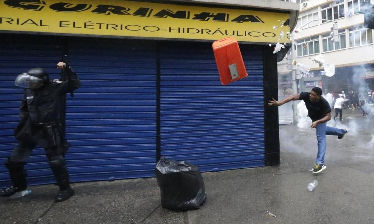 Morador do Pavão-Pavãozinho atira uma lata de lixo sobre policial Foto: RICARDO MORAES / REUTERS