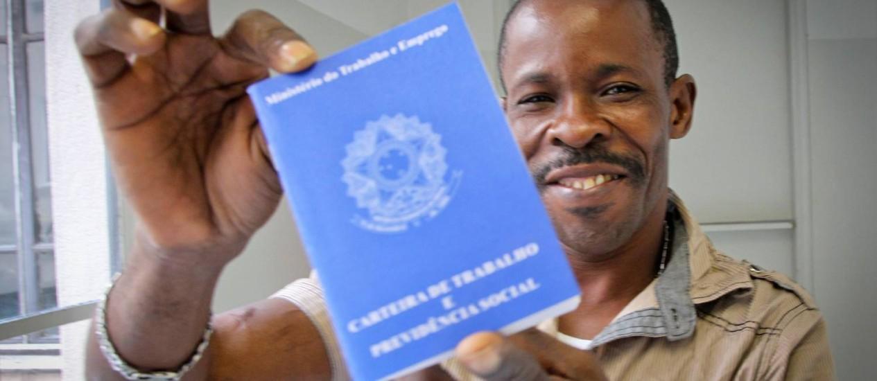 O haitiano Jaccius Pierre com sua carteira de trabalho em SP Foto: Marcos Alves / Agência O Globo