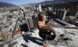 """Em 1994, a construção de um edifício comercial de Caracas foi interrompida. Em 2007, famílias começaram a ocupar o local, e hoje há mais de 3 mil pessoas morando lá. Água e energia elétrica chegam através de """"gatos"""" pagos a organizações que também fazem patrulhas de segurança. O fotógrafo Jorge Silva, da Reuters, passou semanas clicando o local. Na imagem, o morador Gabriel Rivas levanta pesos no 28º andar"""